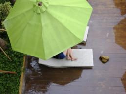 Nainen lepäilee terassilla ison aurinkovarjon alla suojassa vesisateelta.