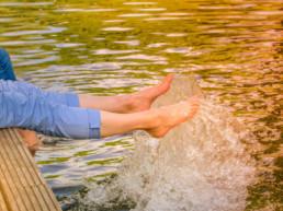 Ihmisiä laiturilla jalat järven vedessä.