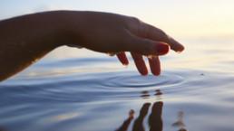 Käsi koskettaa veden pintaa
