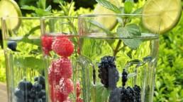 Erilaisia marjoja ja hedelmiä kolmessa vesilasissa