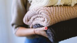 Nainen kantaa pyykkipinoa sylissään.