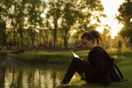 Tyttö istumassa lammen rannalla.