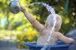 Lapsi kylpe pesuvadissa, heittää kupilla vettä