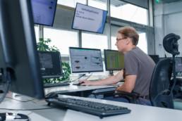 Mies tekee töitä tietokoneella valvomossa.
